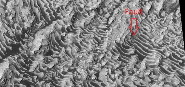 Layers on the floor of Danielson Crater taken under the HiWish program Arrow indicates area of a fault.